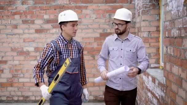 Young male builder in robe, construction helmet and building level