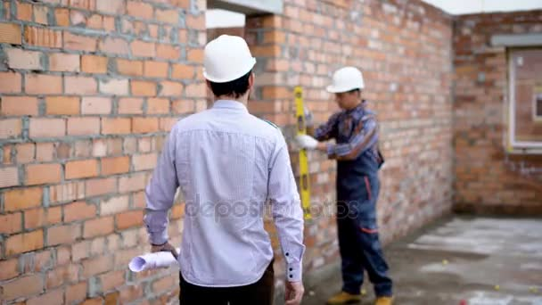 Building wall measurement with building level. Builder and foremen working
