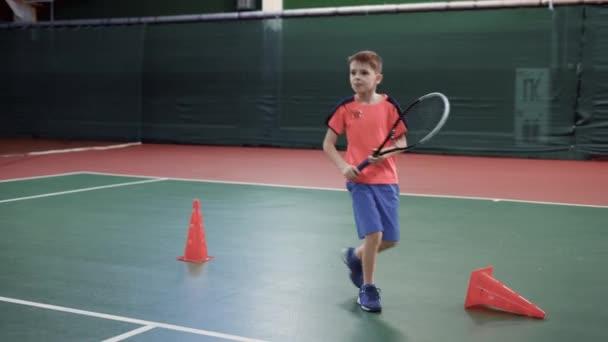 Dospělý chlapec se naučí hrát tenis, chlap v sportovní oblečení bije tenisové míčky s rámus, běhá kolem malé překážky pro vytrvalostní trénink