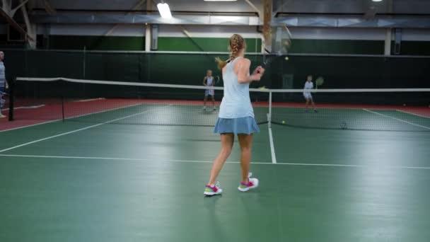 Mladý sportovec honí tenisové míčky během tréninku s její partnery, Žena v obleku sport aktivně vede kolem tenisový kurt