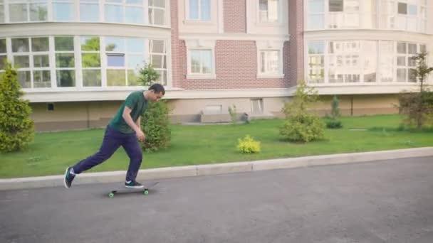 Junger Mann springt auf Skateboard Trick auf Straße üben