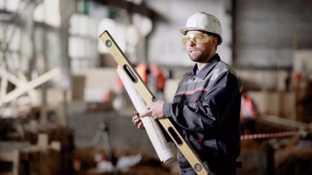 Férfi eszköz és a projekttervben. Férfi dolgozó egységes állandó építők szint és a projekt terv oldalán