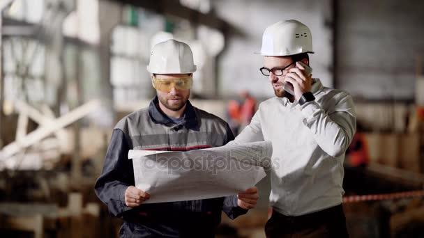 Dělníci na pozemní stavitelství. Vedoucí výstavby mluvící telefon při projednávání plánu projektu na místě s pracovníkem.