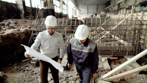 Dva muži pracující s blueprint. Dodavatel a stránky pracovníka vyšetřování blueprint a práci v týmu na pozadí stránek