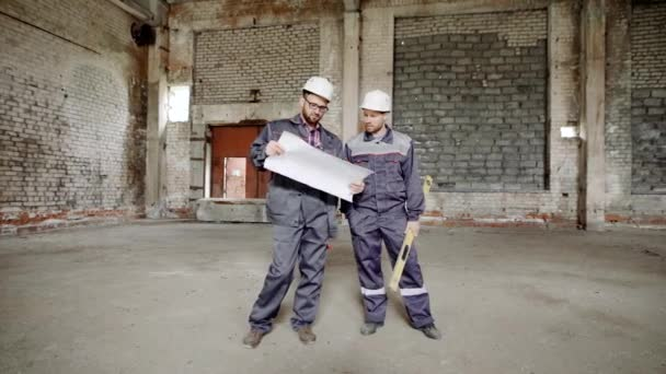 Men on construction with plan. Two construction workers in uniform standing on background of site and exploring blueprint.