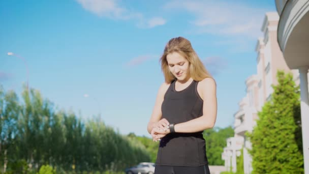 Young sportswoman checking pulse with watch after running on street