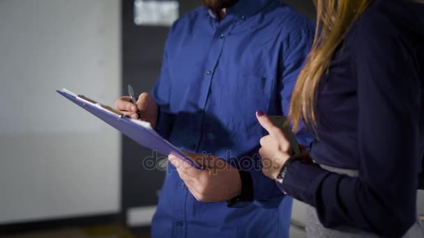 Crop office workers signing papers. Unrecognizable business man and woman standing and signing papers in office.