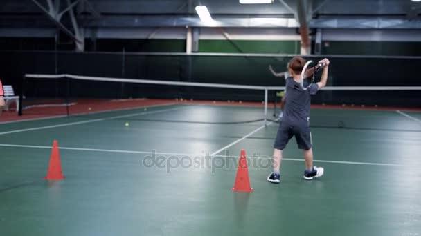 Dva chlapci hrají tenis s starší dívka nebo trenér. Sportovní praxe u soudu
