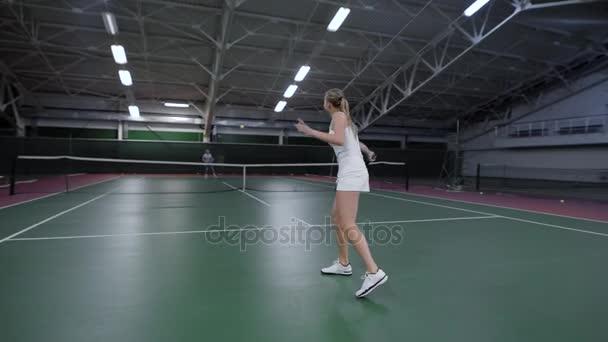 Tenistka hrající na krytý soudu proti mužské hráče
