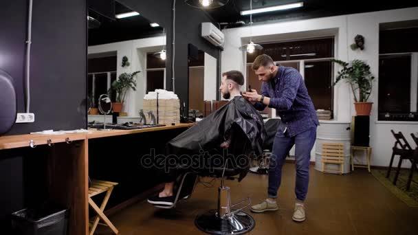 Kadeřnice, použití řezačky na klient sedí v křesle v holičství