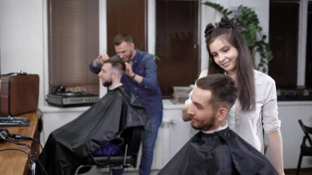 Professional hairdressers making stylish hairdo to men sitting in salon