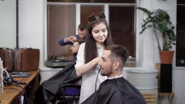 Man and woman working in barbershop making stylish hair to customers sitting in chair
