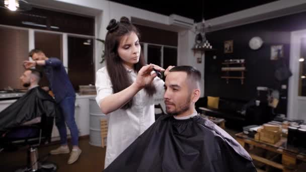 Young female barber making stylish hair to man in salon