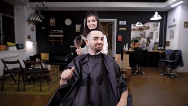 Barber woman showing result of haircut to client sitting in salon