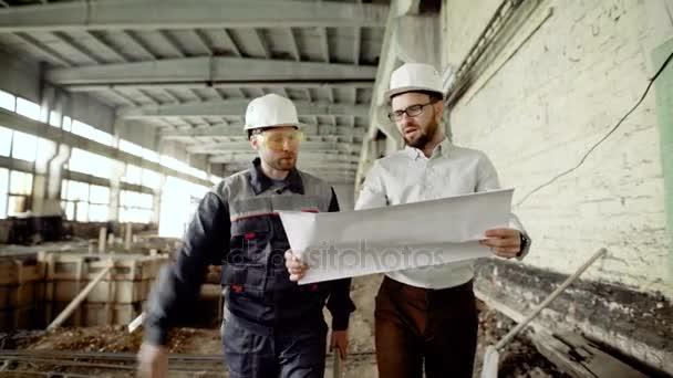 Auditor oblečená v košili a kalhotách chůzi s pracovníkem podél stavební oblasti. Profesionální inspektor drží plánu a diskuse o podrobné údaje o budoucím projektu s stavební superintendent.