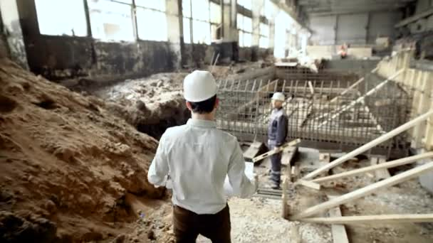 Professional engineers working together on construction site. Chief architect walking to worker standing near formwork of foundation. Builder with level listening to foreman waiting for instructions.