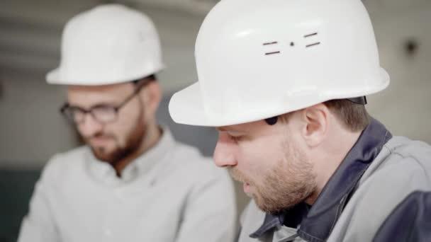 Zblízka se dvou vousatých mužů v ochranné přilby spolupracovat v oblasti stavebnictví. Mistr a pracovník stojí na staveništi. Stavitelé jednají aktuálního projektu a smíchu.