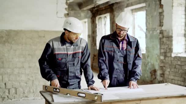 Dva profesionální technici pracují společně u stolu s dokumentace na stavební pozemky. Architekt a foreman stojí na staveništi a zkoumá strukturální kresba