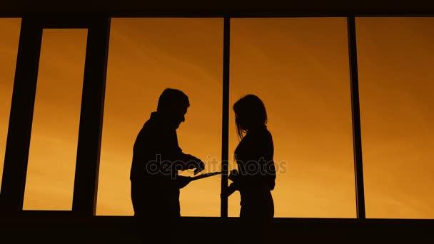 Temné siluety štíhlá žena a muž, který stojí v profilu na twilight poblíž okna. Obrys ženské podnikatelka chůzi a zastavení podepsat dokumenty proti oranžové nebe