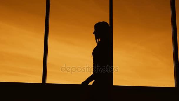 Sötét sziluettje egy hosszú hajú karcsú nő séta a twilight mentén a panorámás padlótól a mennyezetig érő ablak profil. Vázlat a női test ellen narancssárga naplemente ég, a háttérben.
