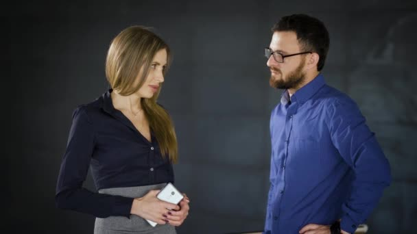Two colleagues are chatting in the office with dark grey wall in the background. Man in blue shirt is communicating with woman in smart suit. Business people are having informal meeting.