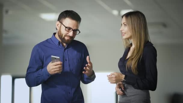 Two colleagues are chatting in the office during coffee break. Man in blue shirt is communicating with woman holding smartphone in hands. Business people are laughing and smiling happily.