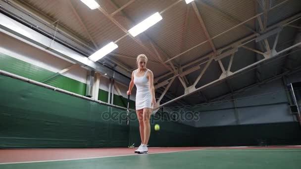 Žena na kurtu zvracel míč při hraní tenisu