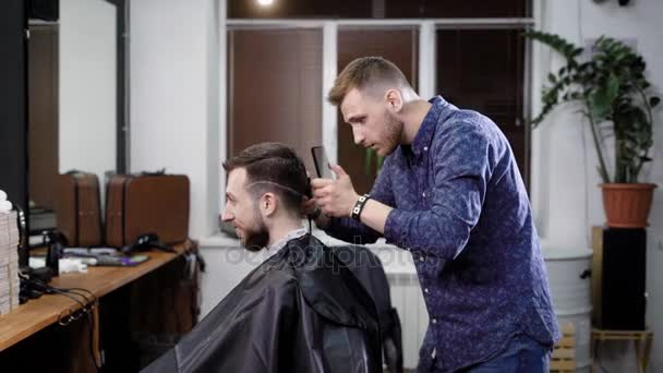 Making haircut. Young bearded man getting haircut by barber while sitting in chair at barbershop