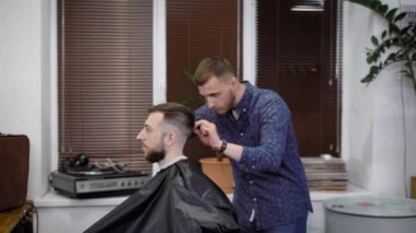 Collective of hairdressers working together. They creating hairstyles. Everyday scene from barbershop