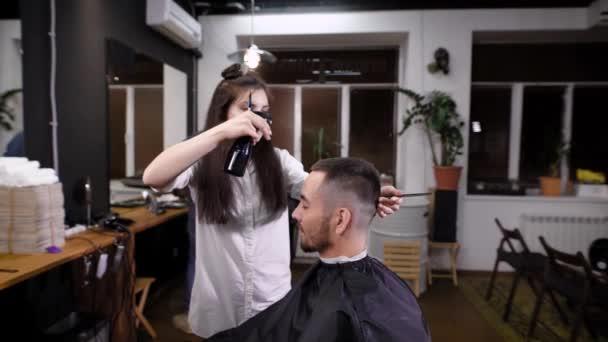 Man hipster visiting barber shop. Woman barber making stylish haircut. View of interior of barber shop