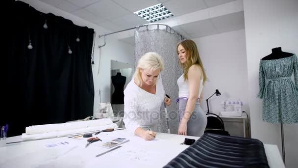 a71a4ac85f3 Две женщины в ателье и создание одежды при выполнении измерений– стоковое  видео