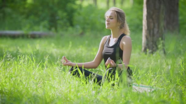 Woman doing yoga outside in the park. She sitting on lotus pose.