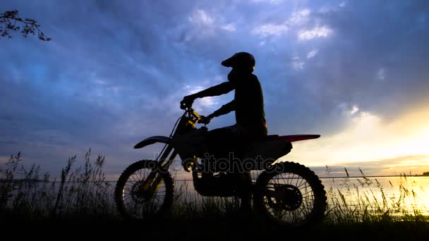 Black silhouette of man posing on motorcycle in sunset