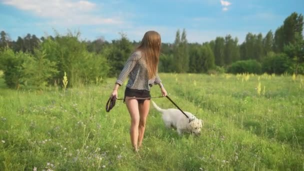 Young attractive sporty woman running with her dog in park at country side.