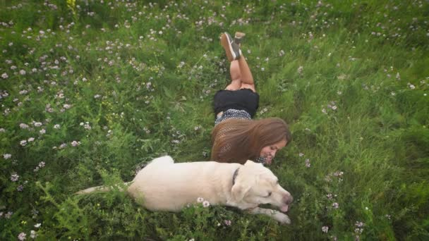 Beautiful woman owner lying on the grass, caressing and petting her labrador dog