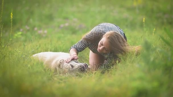 Happy female owner with her dog. She petting her labrador dog lying on the grass