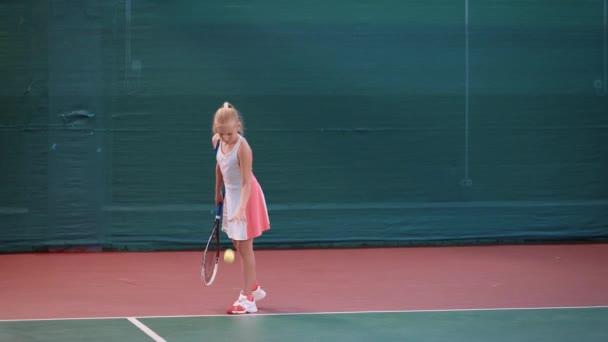 Malá dívka oblečená v sportovní oblečení má trénink na krytých kurtech. Mladé ženy sportovkyně hrají profesionální tenis a skákání žluté koule než udeří jej raketou