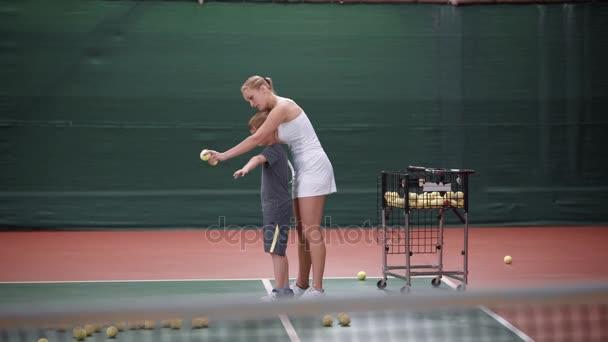 Profesionální tenistka stojící za její malý učeň, držela ho za ruku a ukazuje správný dopad. Mladý sportovec učení na vnitřní dvůr. Chlapec, trénink s trenérem udeření míče