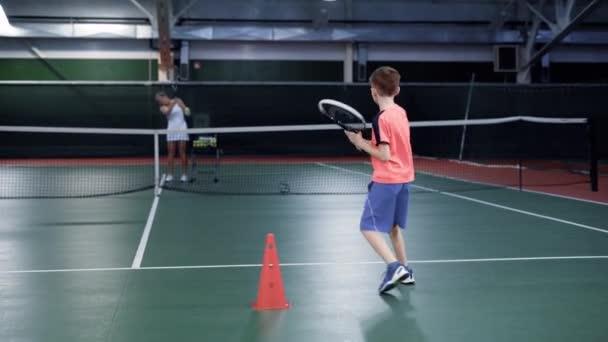 Žena oblečená v bílé sportovní oblečení hraje tenis se svým synem na vnitřní dvůr. Ženské trenér slouží a chlapec se vrací míče raketou pobíhající po speciální síť v rekreační oblasti