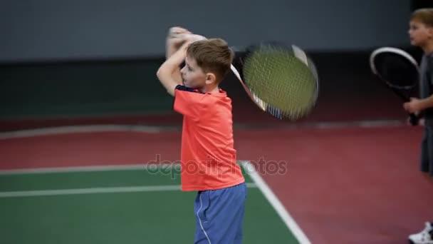 Dva happy boys sloužící a vrácení míče na kurtu raketou. Děti bít předák v tenise s ponaučení. Mladí sportovci učení, hrát sportovní hry v rekreační oblasti