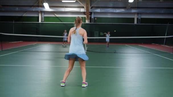 Zadní pohled mladých atletka skákání v rekreační oblasti hrát sportovní hry. Tři šťastné děti s tenisové lekce. Dvě dívky a chlapce slouží a vrácení žlutá koule s rakety