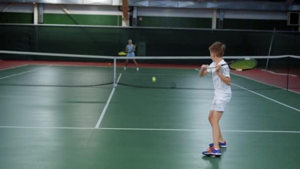Dva mladí sportovci skákání v rekreační oblasti hrát sportovní hry. Tři šťastné děti s tenisovou lekci zlepšování dovedností. Dvě dívky a chlapce slouží a vrácení žlutá koule s rakety