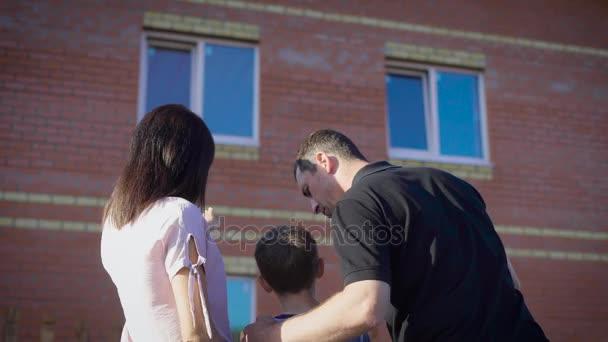 Šťastný pár s dítětem při pohledu na nový byt. Milující rodinu v letní slunečný den zobrazeno moderní dům. Matka otec a syn všeobjímající, diskuse o budovu se třemi okny