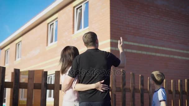 Šťastný pár stojící mimo všeobjímající a při pohledu na nový byt oplocená. Milující rodinu v letní slunečný den zobrazeno moderní dům. Matka otec a syn s třemi okny