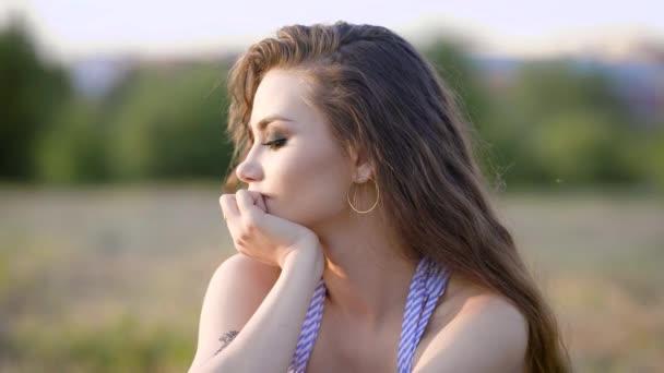 Porträt einer jungen Frau mit hellem Make-up und lockigem Haar, die es genießt, in die Ferne zu blicken, eine Dame sitzt an einem warmen Sommertag in der Natur