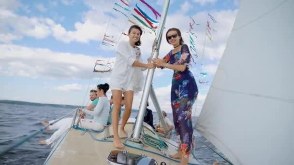 Společnost dovolené přátel, kteří jsou na jachtě plout po moři během malou bouři, šťastné ženy drží na stěžeň a užít si projížďku lodí na vodě