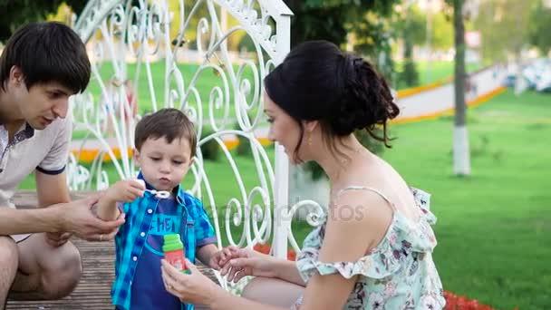 mladý tmavovlasý muž a žena se učí jejich malého syna na ránu bubliny v parku v letním dni