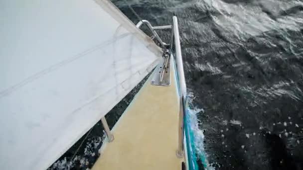 nosu malé plachetnice s bílou plachtou jede tmavé vlny z moře v denní, pohled z vrcholu