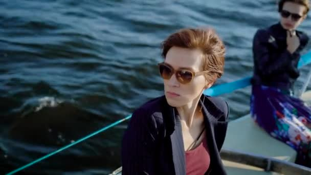serious and thoughtful dark-haired women are wearing sunglasses are sitting on a board of boat in sunny day