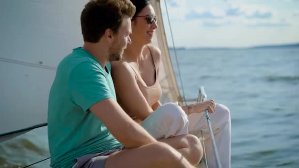 Young man and woman enjoying sunlight while sailing on yacht